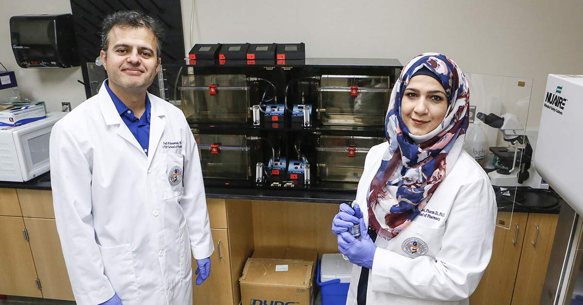 Dr. Fatima Alshool and assistant in a lab, posing for the camera.