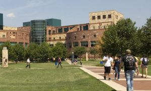 Photo of the UTSA downtown campus with student walking the commons