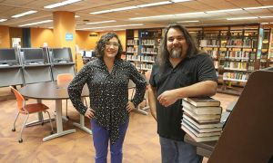 Steve Varela and Angela Lucero are part of a team working to develop Open Educational Resources, pictured standing together in a library.