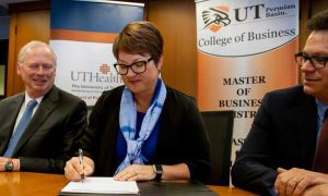 UT Permian Basin President Sandra Woodley at a table signing an agreement with UT Health officials next to her.