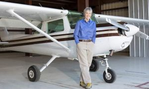 UT El Paso President Heather Wilson stands in an air plane hanger, in front of a small propeller plane.