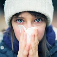 close-up photo of a woman in warm clothes and sneezing into a Kleenex.