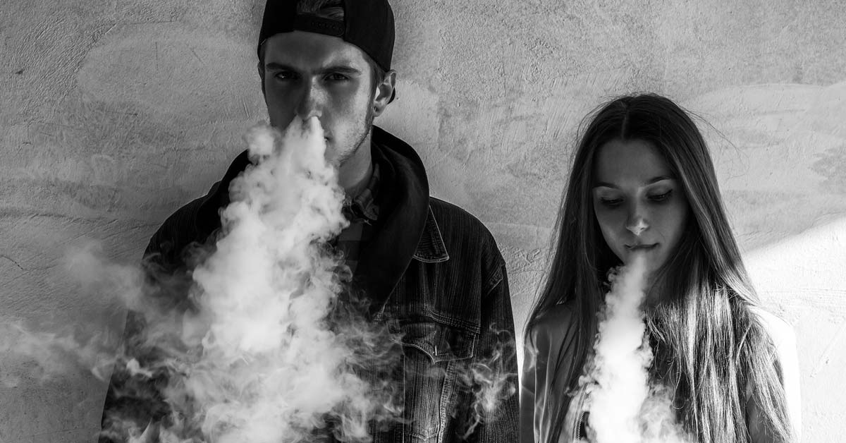 Two young adults, a man and woman, exhaling vaping trail smoke