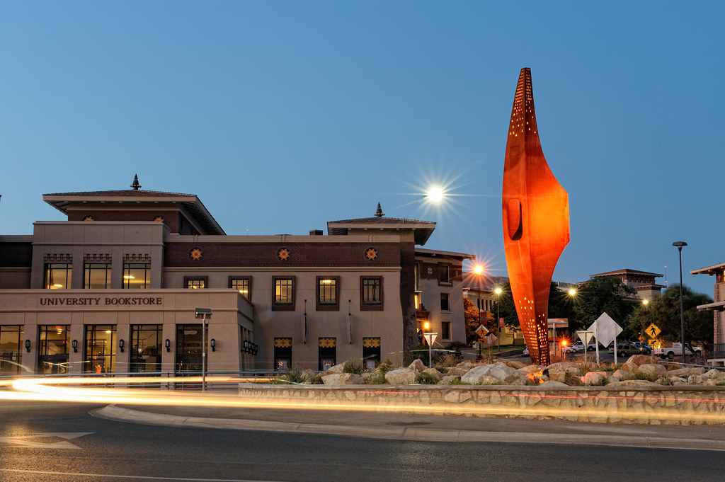 UT El Paso commons area in the evening with the giant pick axe with orange lighting on it
